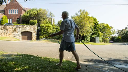 A man waters his garden with a hose in Sydney's Vaucluse.
