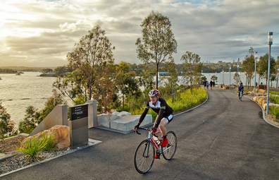 A man and a woman enjoy a bike ride through Barangaroo Reserve in Sydney.