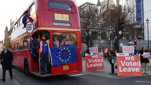 A pro EU campaign bus drives past Vote Leave supporters outside parliament as the Brexit deal continues to divide parliament.