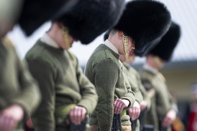 Soldiers from the Welsh Guards bow their heads as they rehearse for Britain's Prince Philip's funeral on the Drill Square at the Army Training Centre Pirbright in Woking, Surrey, England Wednesday April 14, 2021.