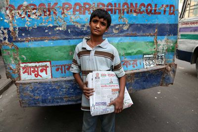 Morning newspaper seller in the streets of Dhaka, Bangladesh (2014).