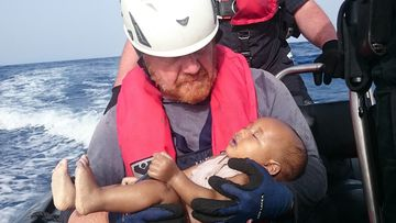 A Sea-Watch humanitarian organization crew member holds a drowned migrant baby, during a rescue operation off the coasts of Libya. (AAP)