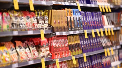 Tempting sweet treats and soft drinks are a regular sight near the checkouts of major Australian supermarkets. (AAP file)