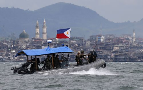 In this 2017 photo, Philippine Navy commandos ride on a gunboat as it patrols the periphery of Lake Lanao. Smoke rises from the main battle area where pro-Islamic group militants made a final stand amid a massive military offensive of Marawi city in southern Philippines.