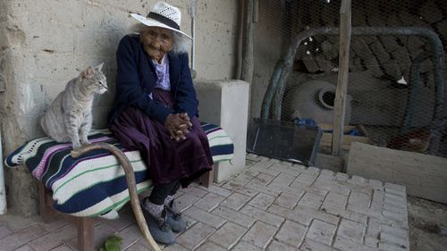 """In this Aug. 23, 2018 photo, 117-year-old Julia Flores Colque and her cat """"Minina"""" sit outside their home in Sacaba, Bolivia."""