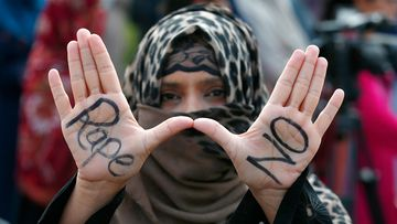 A supporter of the religious group 'Jamaat-e-Islami flashes a 'Rape No' signs during a demonstration to condemn the incident of rape on a deserted highway, in Islamabad