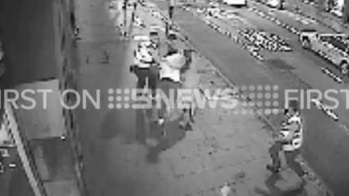 Several passers-by seem to be caught up by the fight. (9NEWS)