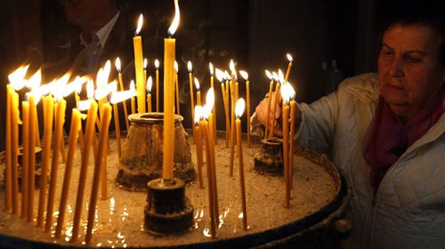 An Orthodox Bosnian Serb woman lights candles during the Easter service in Sarajevo Cathedral, in Sarajevo, Bosnia and Herzegovina. (AP).
