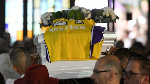 A LA Lakers gurnsey of the late Kobe Bryant, with the words 'Play'N In Heaven' is seen on the coffin of Antony as it leaves the funeral.
