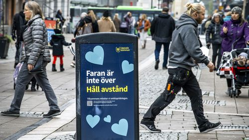 """People pass a trash can with a sign reading """"The danger is not over - Keep your distance"""" in a pedestrian street in central Uppsala, Sweden, Wednesday, Oct. 21, 2020"""