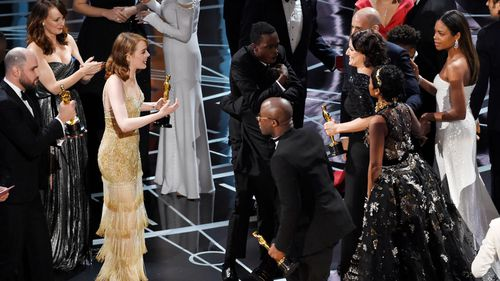 The cast and crew of La La Land welcome those of Moonlight to the stage after the latter was announced as the winner. (AAP)