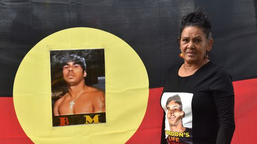 The mystery surrounding the disappearance of Gomeroi man Gordon Copeland has prompted community action. Stella Fernando stands next to a photo of her missing grandson, Gordon.