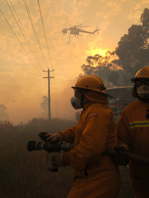 Country Fire Authority (CFA) fire fighters wait for the fire to reach their defence line along Glenfern Rd, in Upwey, east of Melbourne.