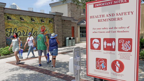 Signs remind patrons to wear masks and other protocols because of the coronavirus pandemic as they stroll through the Disney Springs shopping, dining and entertainment complex Tuesday, June 16, 2020, in Lake Buena Vista, Fla. (AP Photo/John Raoux)