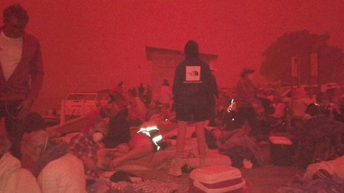 People are pictured on Mallacoota beach, ready to escape into the water if the bushfire moves into the town.