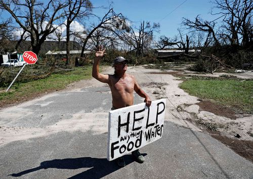 Michael Williams, 70, waves to passing motorists while looking for food and water as downed trees prevent him from driving out of his damaged home with his family in the aftermath of Hurricane Michael in Springfield, Florida.