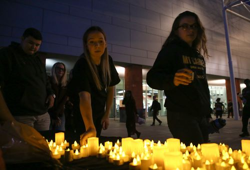 Mourners are handed out electric candles during a candlelight vigil at the University of Nevada Las Vegas. (AAP)