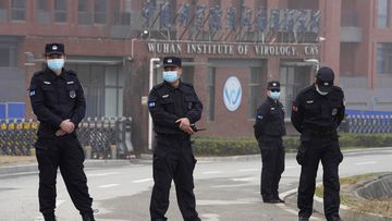 Security personnel gather near the entrance of the Wuhan Institute of Virology in February 2021.
