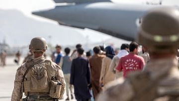 US Marines guide evacuees on to a US Air Force Boeing C-17 Globemaster III at Hamid Karzai International Airport in Kabul.
