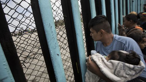 A member of the Central American migrant caravan, holding a child, looks through the border wall toward a group of people gathered on the U.S. side. (AP)