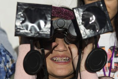 A girl tests special binoculars in the local park.