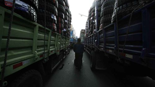 A Chinese truck driver who drives goods to North Korea walks between full-loaded trucks in Dandong. (AAP)
