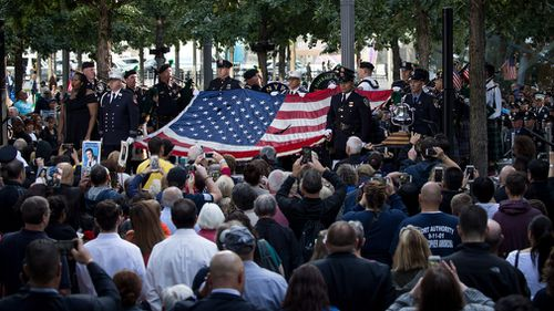 Firefighters hold up a flag at in New York City. (AFP)