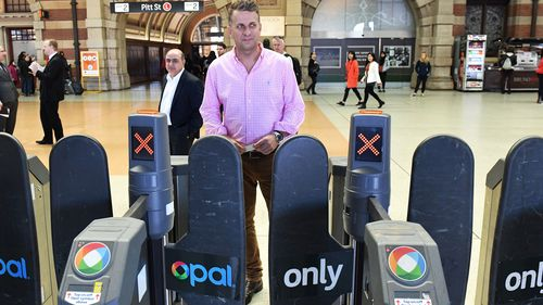 NSW Minister for Transport and Infrastructure Andrew Constance goes through an Opal Card turnstile after a press conference at Central Station