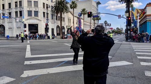 A tourist poses for a photo on Hollywood Boulevard. (9NEWS/Ehsan Knopf)