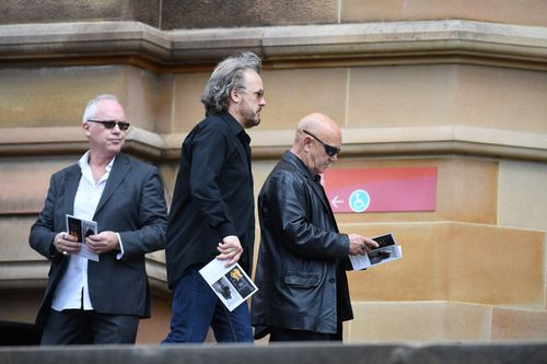 AC/DC alumni Mark Evans (middle) and Angry Anderson (right) attend St Mary's Cathedral. (AAP)