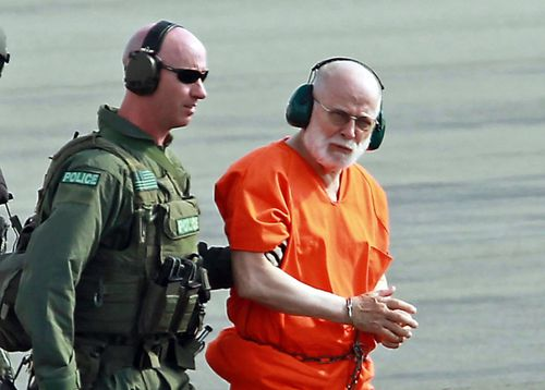 In this 2011 file photo James 'Whitey' Bulger, right, is escorted from a US Coast Guard helicopter to a waiting vehicle at an airport in Plymouth. Picture: AP