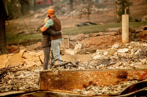 Chris and Nancy Brown embrace while searching through the remains of their home, leveled by the Camp Fire, in Paradise.