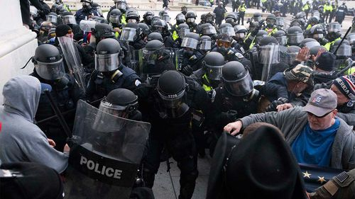 U.S. Capitol Police push back rioters trying to enter the Congress building.