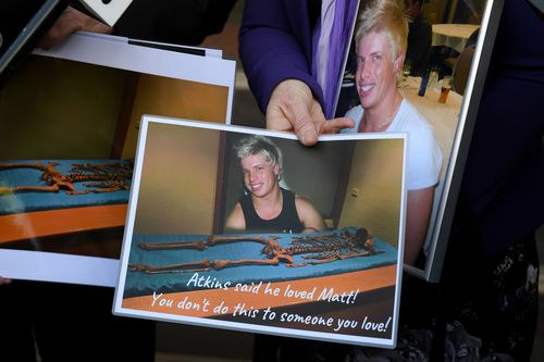 Mark and Faye Leveson hold photographs of their son Matthew's skeletal remains at the coronial inquest. (AAP)