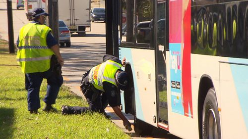 Police inspect the damage to the bus after the crash on Canterbury Road. (9NEWS)