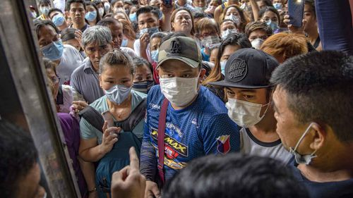 Filipinos hoping to buy face masks crowd outside a medical supply shop that was raided by police for allegedly hoarding and overpricing the masks, as public fear over China's Wuhan Coronavirus grows, on January 31, 2020 in Manila, Philippines.