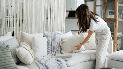 Woman organising and tidying up the cushions on the sofa in the living room at home