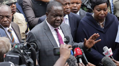 Kenya's Interior Minister Fred Matiangi speaks to reporters outside the complex.