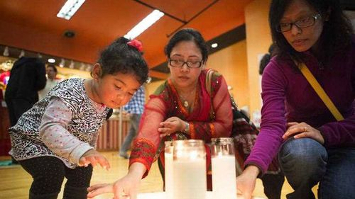 Support has flowed in from around the world. Here, toddler Samataa Shrestha helps her mother Pragya place a small candle onto a plate with friend Beenu Maharjan during a community gathering and prayer organised by the Nepal Seattle Society in Washington state. (AP/Seattle Times)