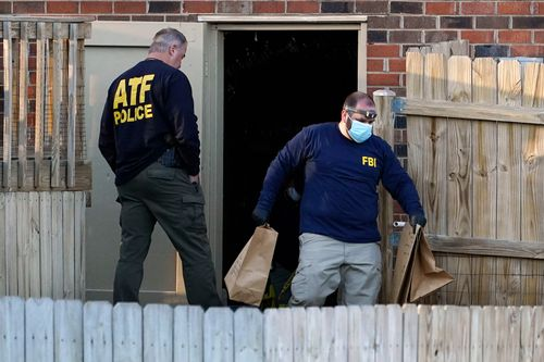 Investigators remove items from the basement of a home