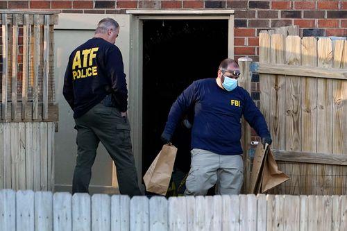 Penyelidik memindahkan barang-barang dari ruang bawah tanah sebuah rumah