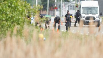 A line of police officers look for evidence at the scene of the car crash in London, Ontario which killed four members of the same family.