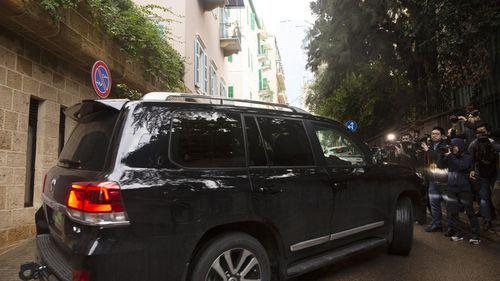 Journalists film a vehicle leaving the home of former Nissan Chairman Carlos Ghosn in Beirut, Lebanon, Thursday, Jan. 2, 2020. Turkish authorities have detained seven people as part of an investigation into how Ghosn, who skipped bail in Japan, was able to flee to Lebanon via Istanbul, Turkish media reported Thursday.