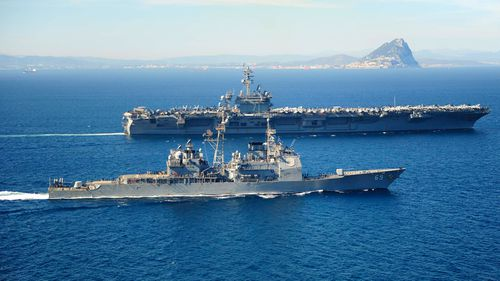 The Ticonderoga-class guided missile cruiser USS Vicksburg  escorts the Nimitz-class aircraft carrier USS Theodore Roosevelt by the Rock of Gibraltar in March, 2015.  The USS Theodore Roosevelt is now sailing in the South China Sea.