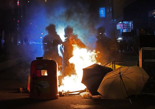 Journalists stand next to fire set by protesters at a main street in Hong Kong.