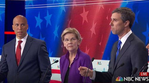 Cory Booker and Elizabeth Warren look on as Beto O'Rourke starts speaking in Spanish.