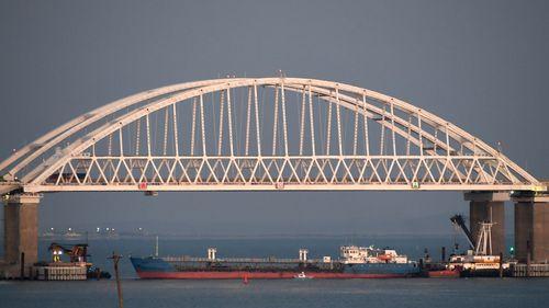 A Russian tanker under the the Kerch bridge blocks the passage to the Kerch Strait near Kerch, Crimea. The Ukrainian Security Service (SBU) said in a statement Thursday July 25, 2019, that it has seized the Russian tanker moored in a Ukrainian Black Sea port. (AP Photo)