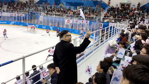 A Kim Jong Un impersonator walks in front of fans waving a unification flag at the Korea-Japan women's ice hockey. (AAP)