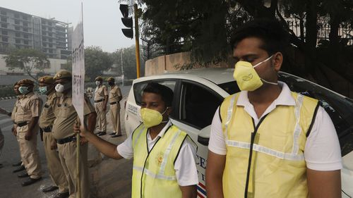Volunteers and policemen wear pollution masks and stand at a busy crossing with the banner saying obey odd and even, remove pollution, in New Delhi.
