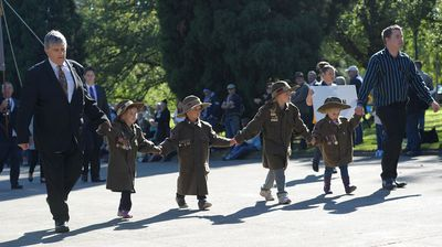 A family marchers towards the Shrine of Remembrance during the Anzac Day march in Melbourne. (AAP)